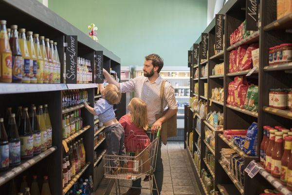 man shopping with two kids in supermarket