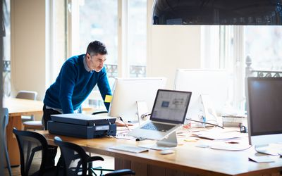 Businessman standing by desk working on a computer