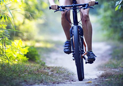 Mujer con rodilla ensangrentada en bicicleta
