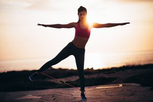 Young fit woman doing balance exercise with resistance band outdoors