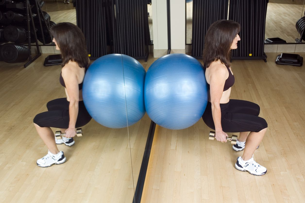 woman pushing an exercise ball against a wall