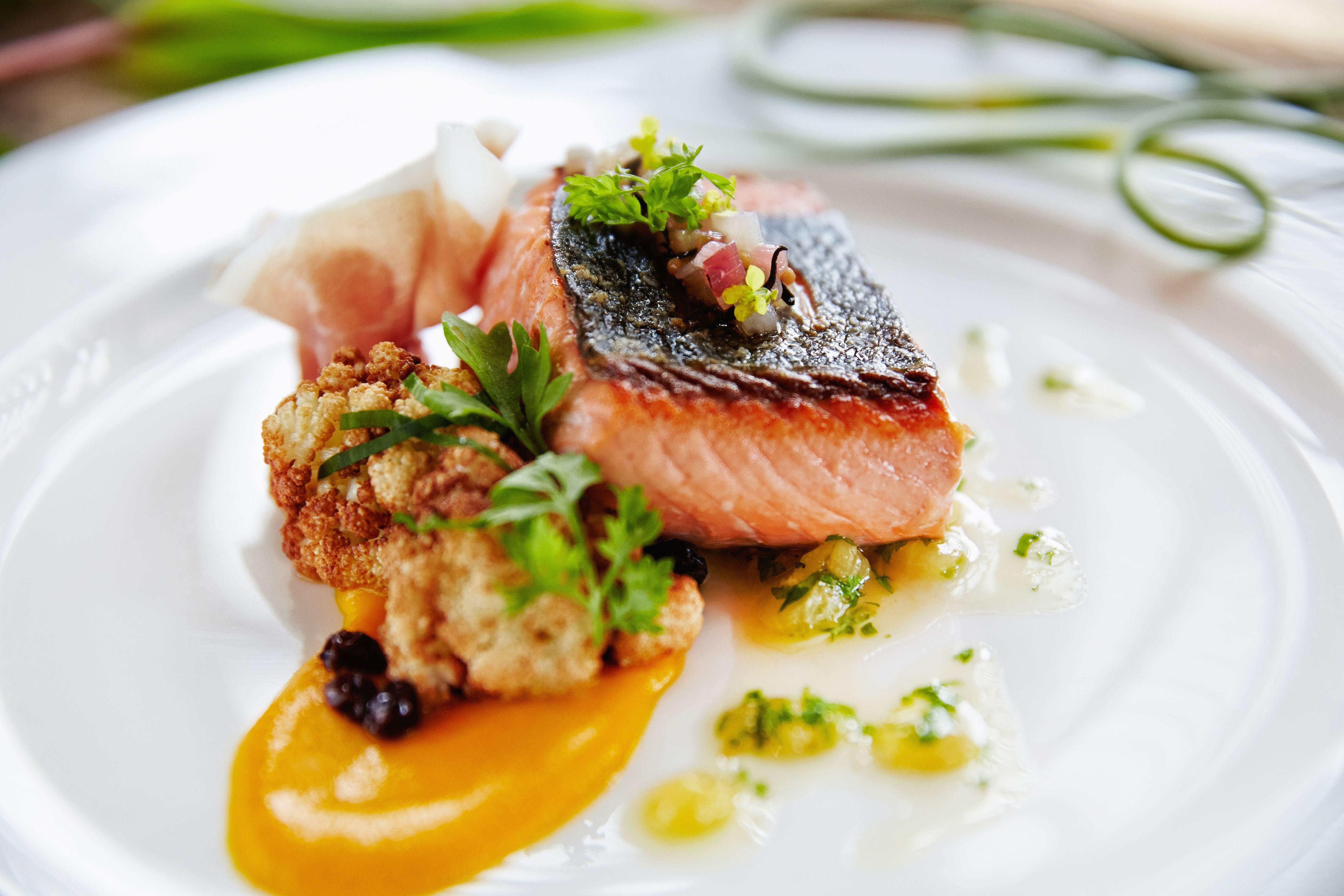 Cerca del plato de pescado fresco a la parrilla y salsa