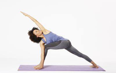 Woman doing revolved side angle pose on yoga mat