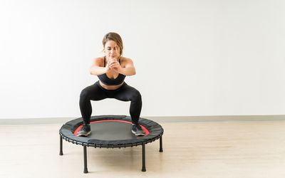 Woman using trampoline for rebounding exercise