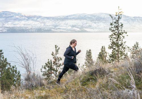 Mujer caminando por fitness cuesta arriba en un sendero de montaña a lo largo de la costa