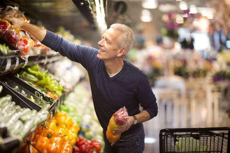 man choosing vegetables in store