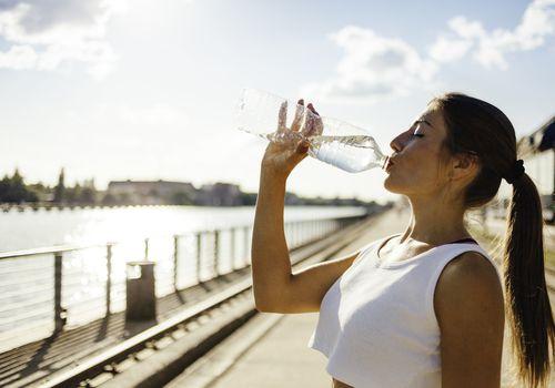 Mujer corriendo mientras bebe agua
