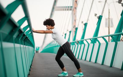 Athletic, young woman exercising on city bridge