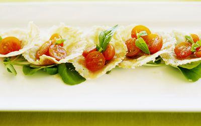Parmesan crisps with sunburst cherry tomatoes, basil and sea salt, close-up