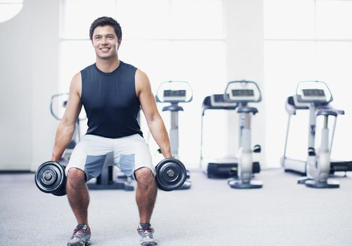 Smiling man doing squats with dumbbells in gymnasium