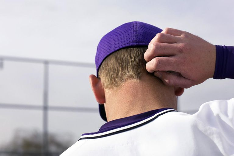 Teenage boy (16-18) baseball player scratching head