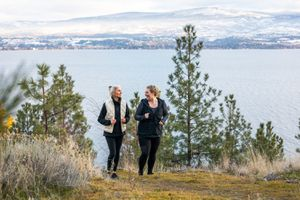 two women walking and talking during a hike in the woods