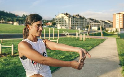 Young woman performing tennis elbow and wrist stretch