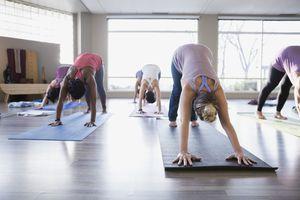 Women practicing downward facing dog in yoga class