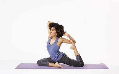 Woman sitting on yoga mat in mermaid pose