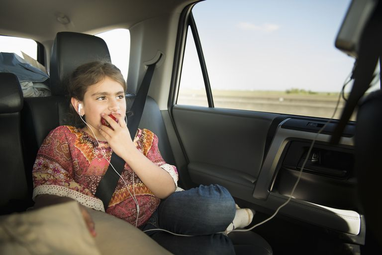 Mixed race girl eating apple in car