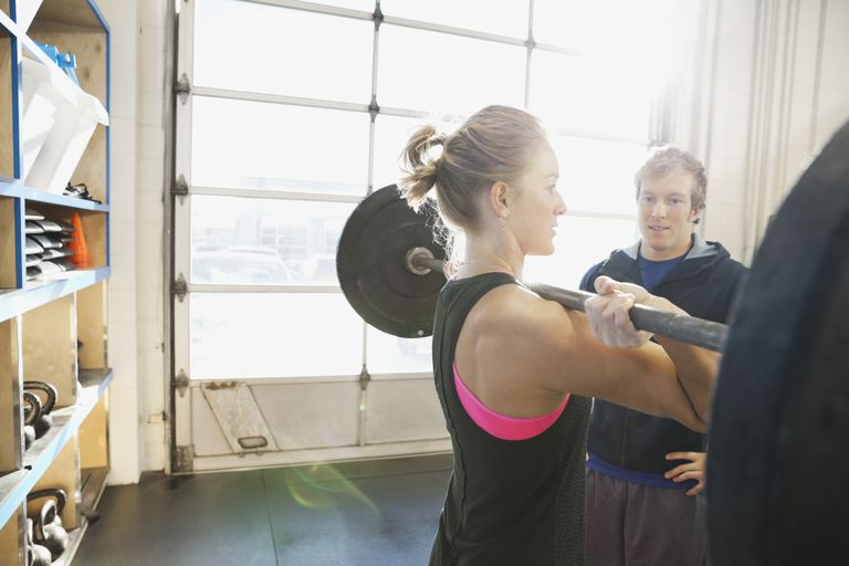 male trainer overseeing female athlete doing clean and jerk lift with barbell