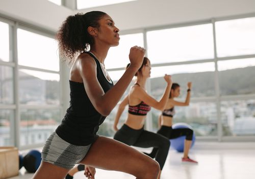 Three women perform a high-intensity workout in a well-lit studio.