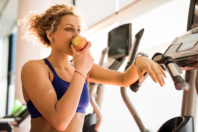 Athletic woman eating apple and in a gym.