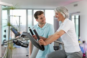 woman exercising with trainer at gym
