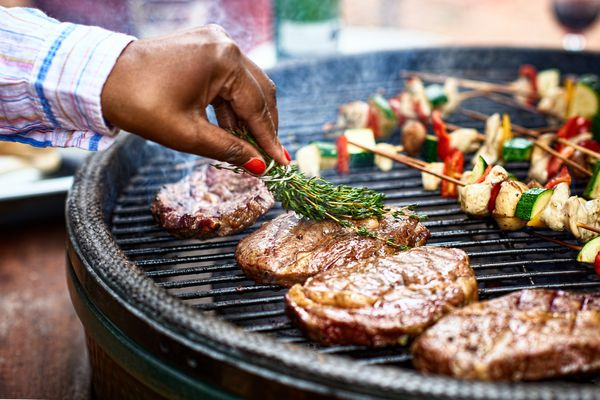 Woman basting meat on barbecue with fresh herbs