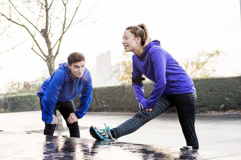 female and male runners stretching outdoor.