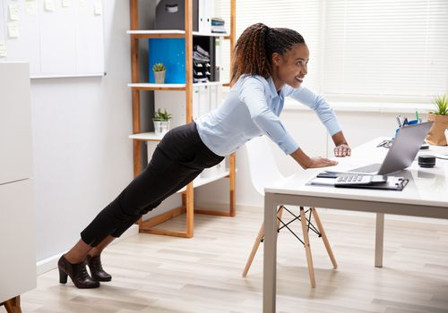 woman performing exercise at desk