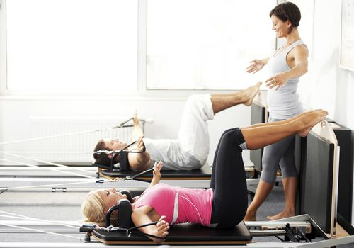 Couple on Pilates reformer being instructed by teacher