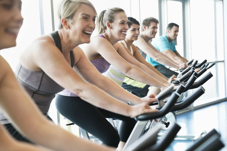 People exercising on stationary bikes in fitness class.