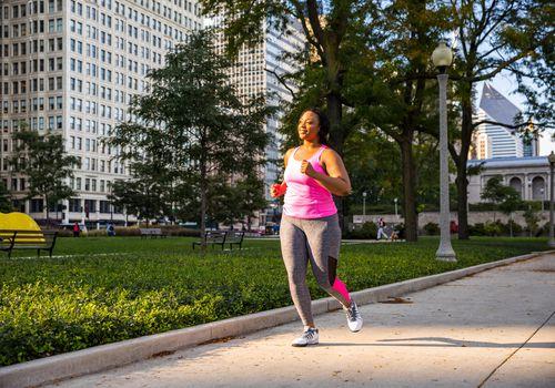 Mujer que corre en la acera en una ciudad