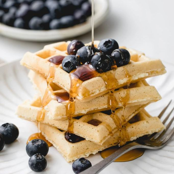 Waffles topped with blueberries and maple syrup