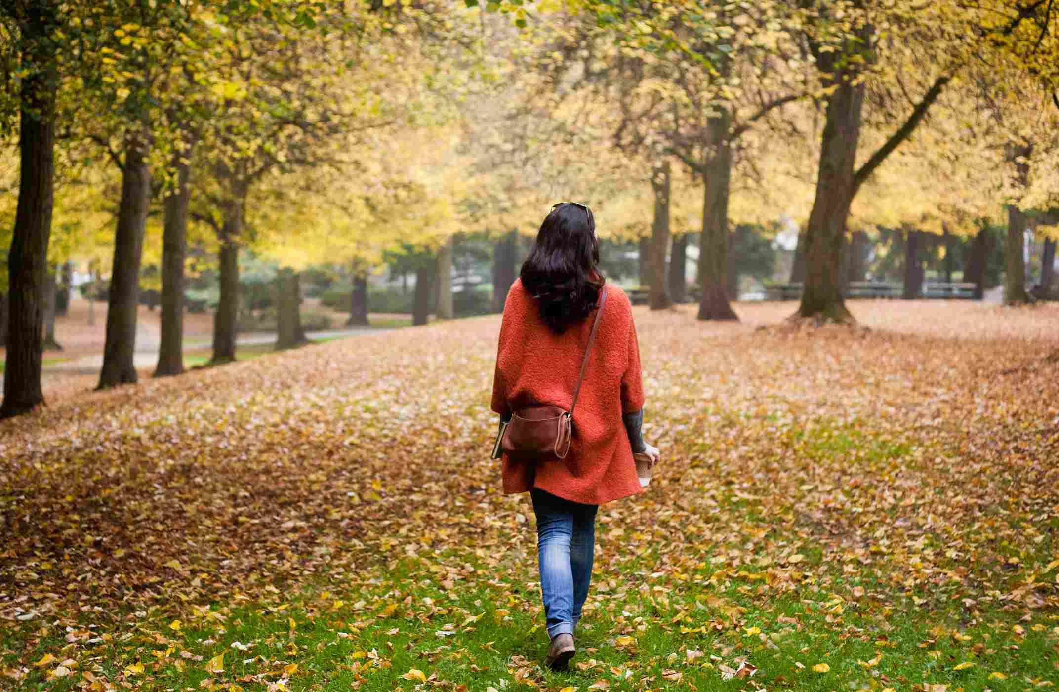 Woman walks alone through leaves