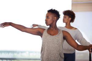 Two women dancing at a barre, arms stretched out