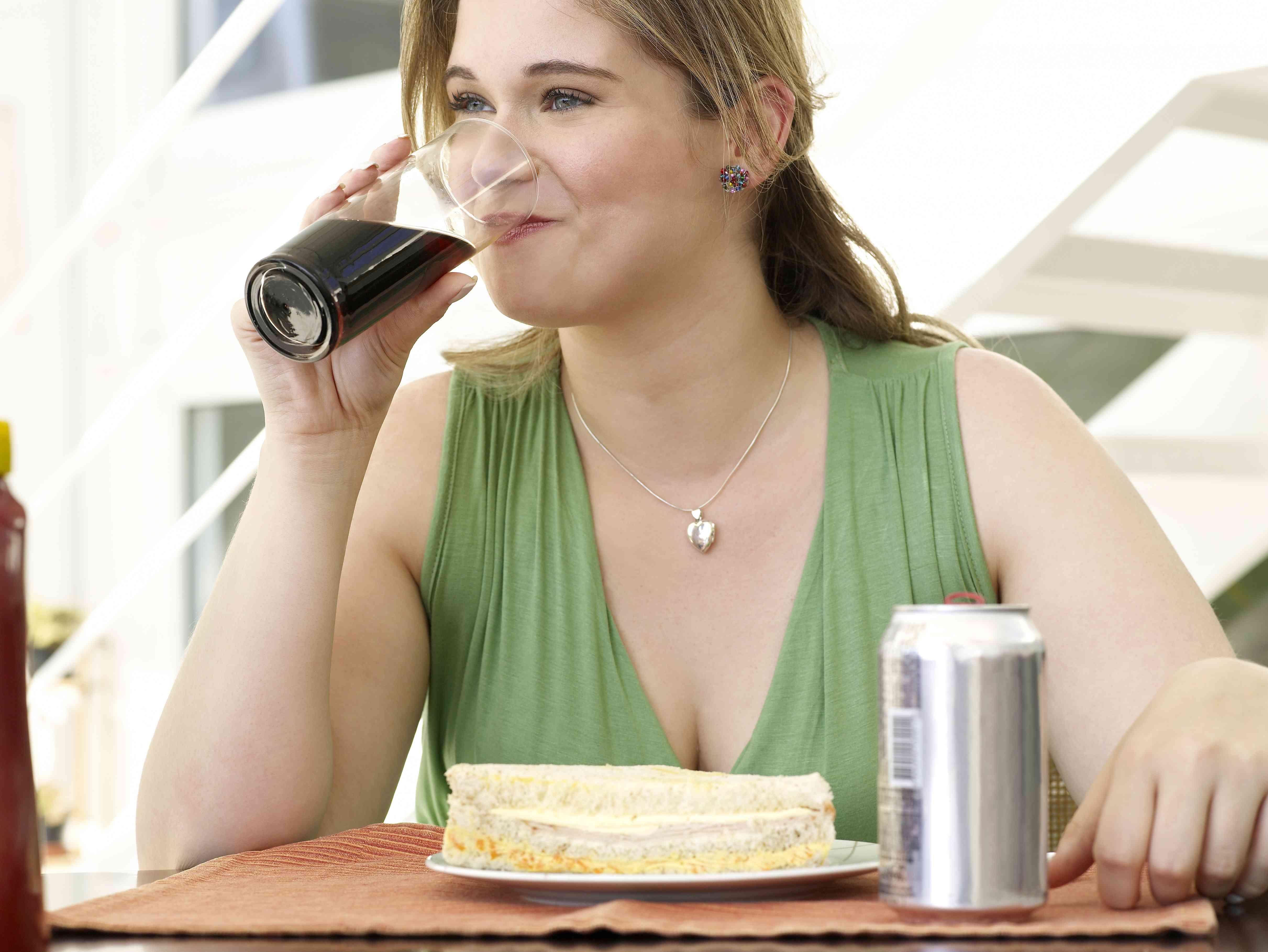 Mujer joven bebiendo un refresco