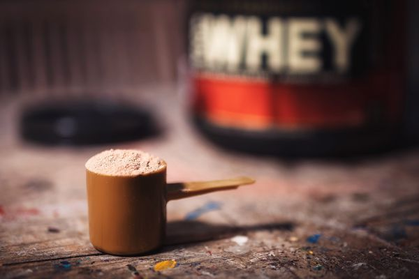 Scoop of protein powder with bottle in the background