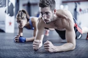 Man and woman in plank position, man with facial hair and bulkier muscles due to increased testosterone
