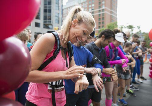 Sonriente corredor de maratón femenino listo, preparando reloj inteligente en la línea de salida en la calle urbana