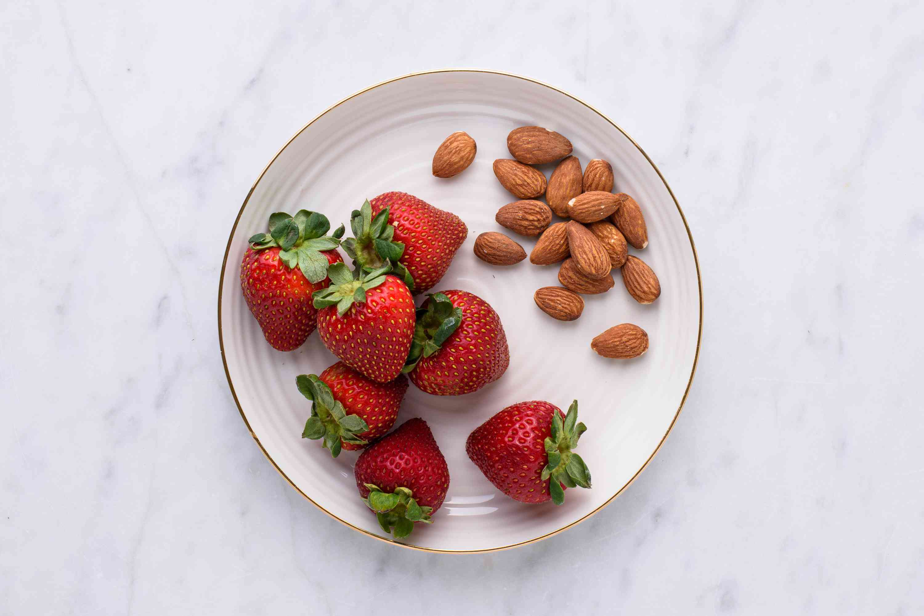fresh strawberries and almonds on a plate