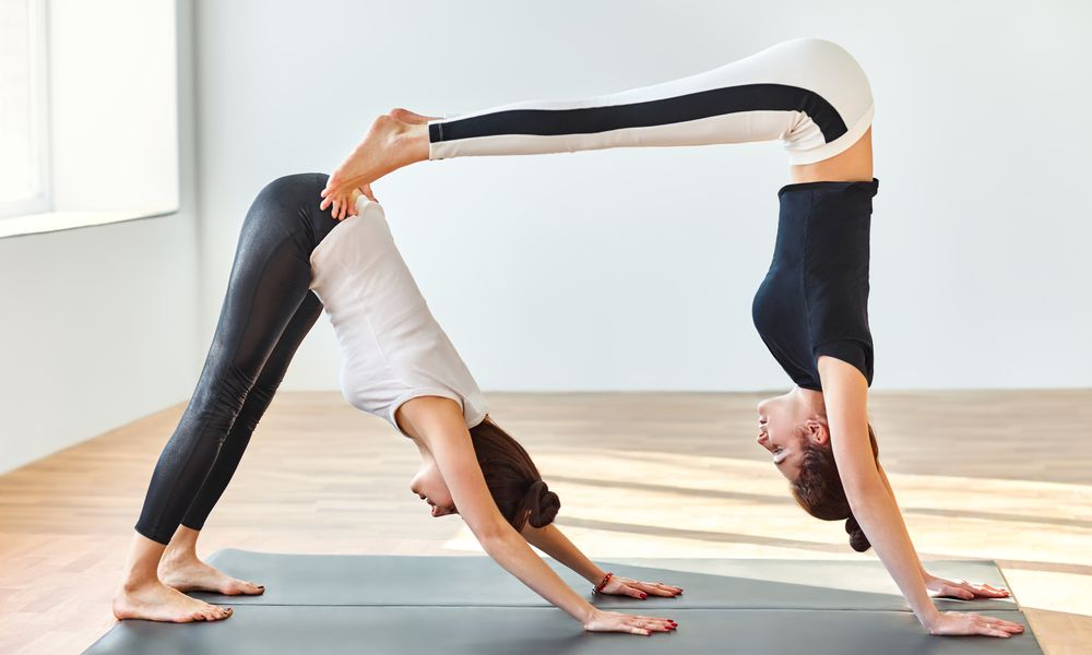 Two yoga partners performing couples yoga