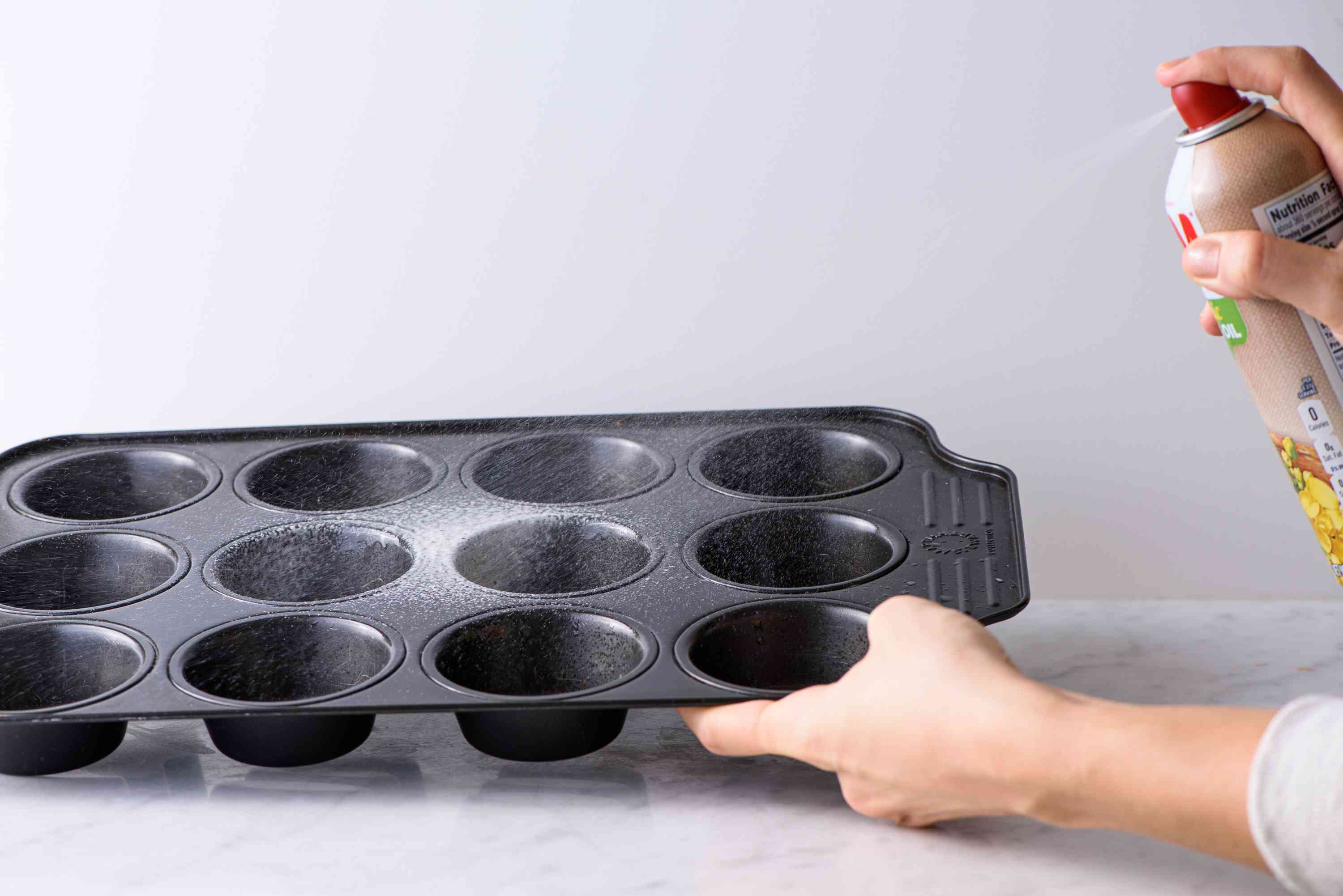 spraying cooking spray into a muffin tin