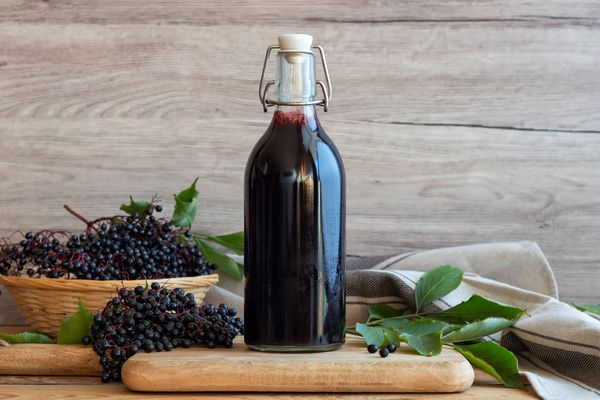 bottle of elderberry syrup on a wooden table