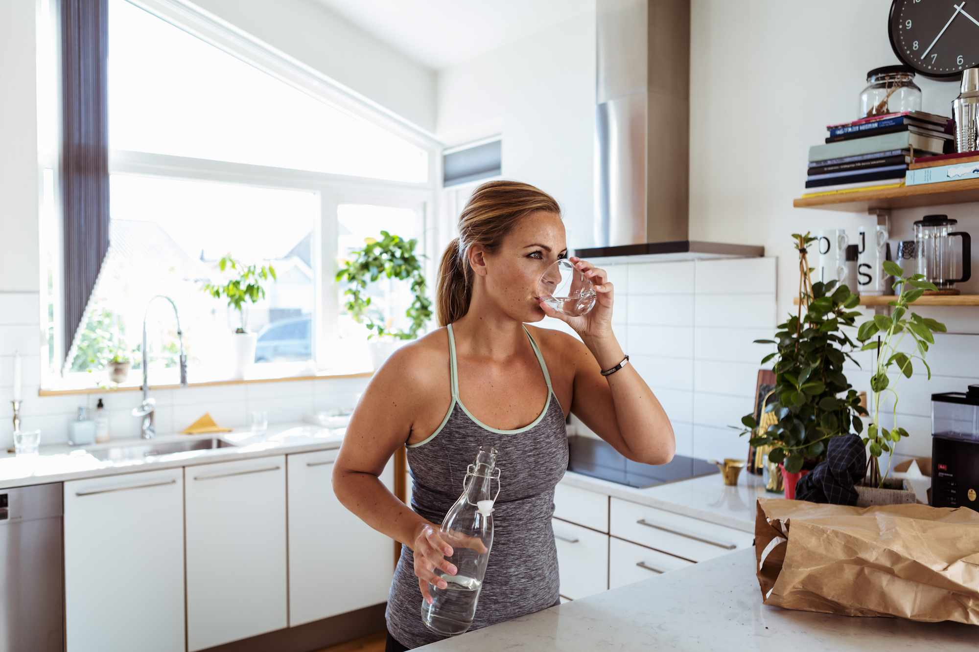 Mujer bebiendo agua en la cocina