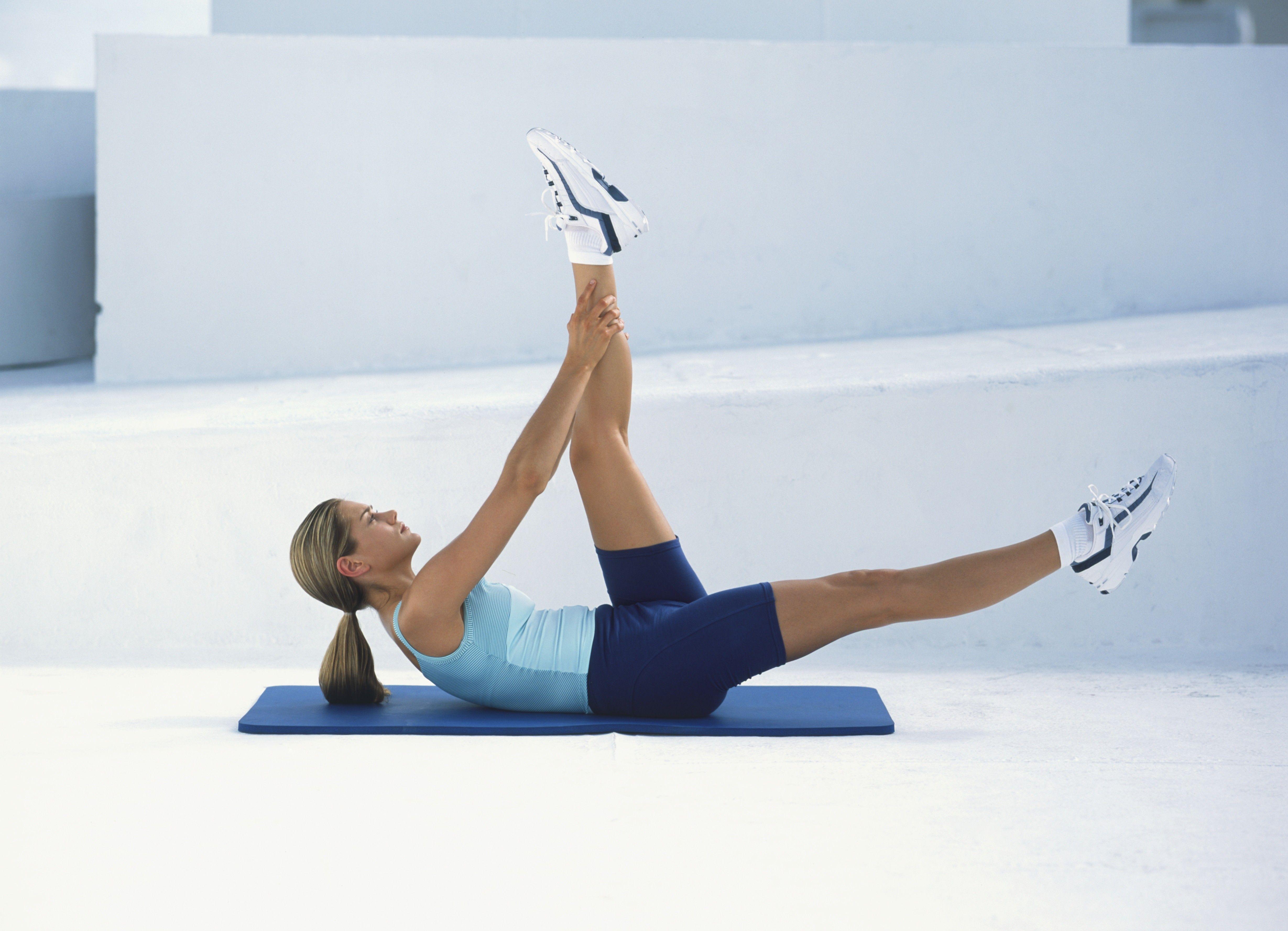 Mujer en pantalones cortos de ciclismo y un chaleco acostada de espaldas sobre una colchoneta de ejercicios, con la cabeza levantada mientras tira de una pierna recta hacia ella, la otra estirada en el aire frente a ella, vista lateral.