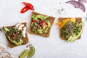 Plant based colorful vegan snack, variety of avocado toasts - stock photo
