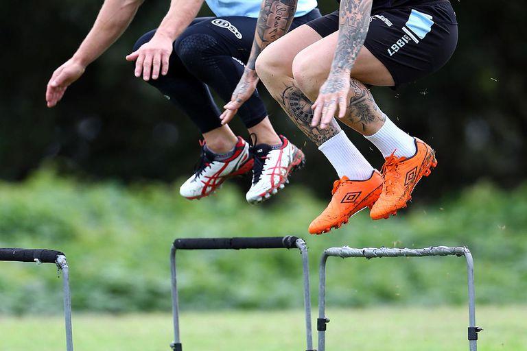 John Morris and Todd Carney jump hurdles during a Cronulla Sharks NRL training session at Sharks Stadium on April 8, 2014 in Sydney, Australia.