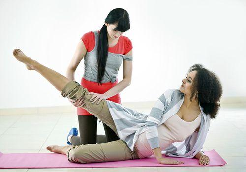 Mujer embarazada con su entrenador físico
