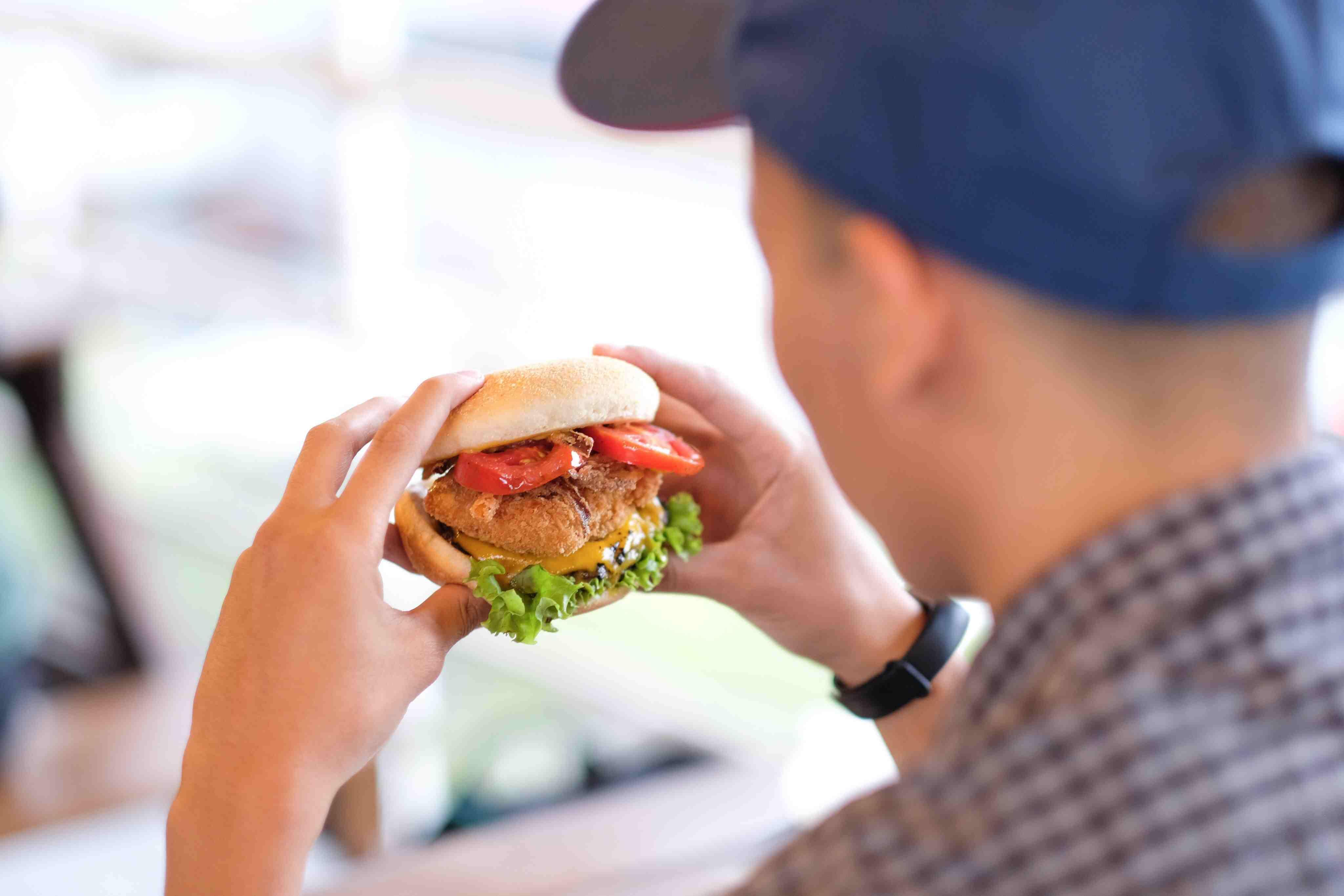 Primer plano del hombre comiendo hamburguesa