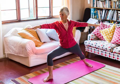 old woman doing yoga in her living room
