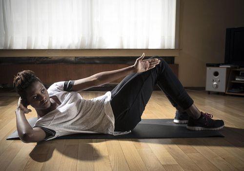 Joven mujer negra (28) en su departamento en Strombeek (Bélgica), haciendo ejercicio