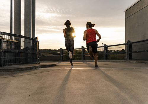 Couple running outside at sunset.